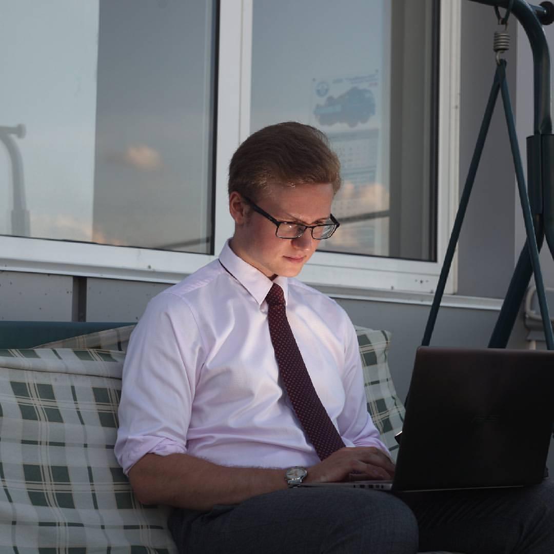 Антон Щукарев с ноутбуком на террасе